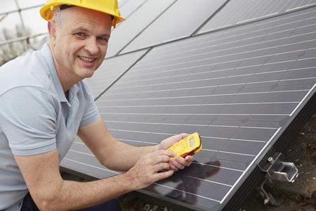 Ingenieur Installieren der Sonnenkollektoren auf dem Dach des Hauses