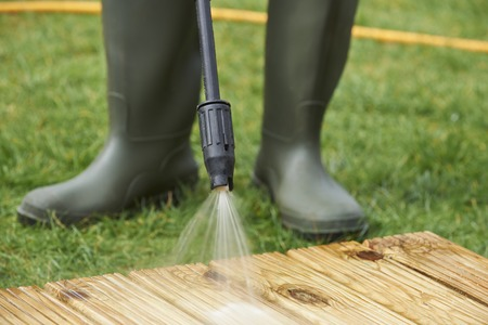 galoshes: Man Washing Wooden Decking With Pressure Washer Stock Photo