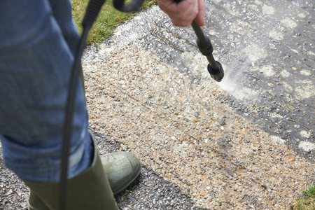 pressure: Man Washing Concrete Path With Pressure Washer Stock Photo