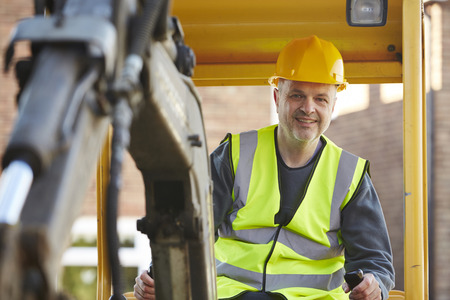 safety equipment: Construction Worker Operating Digger On Site Stock Photo
