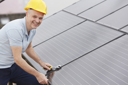 solar panel roof: Engineer Installing Solar Panels On Roof Of House