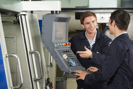 mach: Engineer Instructing Trainee On Use Of Computerized Cutting Mach