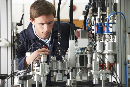 ingeniero: Engineer Working On Complex Equipment In Factory