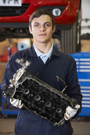 apprentice: Apprentice Machanic Holding Engine Block In Garage Stock Photo