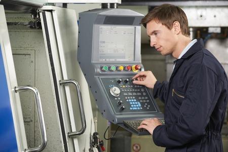 Ingeniero que usa el ordenador controlado corte de la máquina