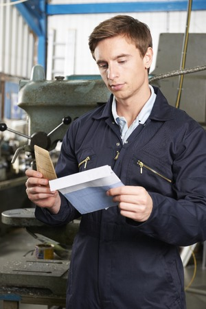 minimum wage: Factory Worker Opening Wage Packet Stock Photo