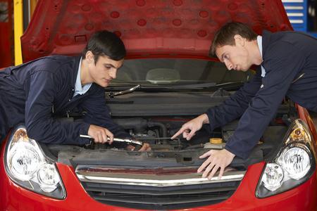 trainee: Mechanic Helping Trainee To Fix Engine