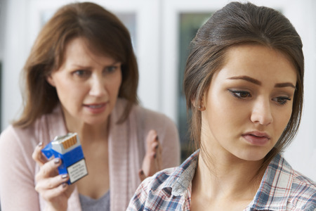 mature smoking: Mother Confronting Daughter Over Dangers Of Smoking Stock Photo