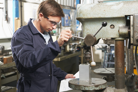 protective eyewear: Engineer Using Drill In Factory Workshop Stock Photo