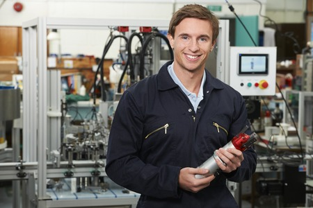happy worker: Portrait Of Engineer Holding Component In Factory