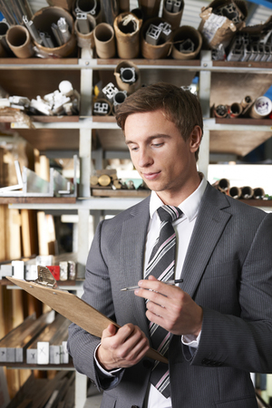 engineering clipboard: Businessman Checking Stock In Warehouse