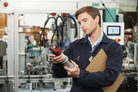 manufacturing equipment: Engineer Inspecting Component In Factory