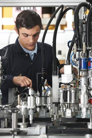 trainee: Trainee Engineer Working On Machinery In Factory Stock Photo