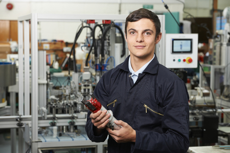 inspecting: Apprentice Engineer Checking Component In Factory