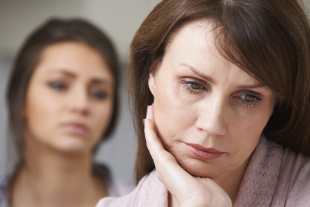 mum and daughter: Depressed Mother With Teenage Daughter Stock Photo