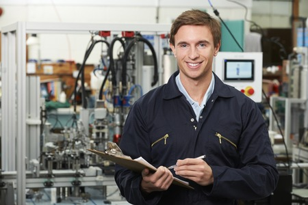 happy workers: Engineer Holding Clipboard In Factory