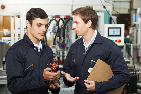 engineering clipboard: Engineer And Apprentice Discussing Component In Factory