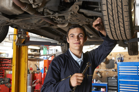 motor transport: Apprentice Mechanic Working On Car