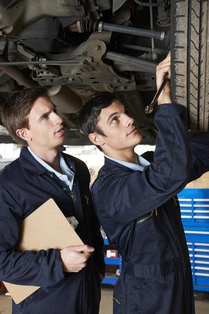 trainee: Mechanic And Trainee Working Under Car