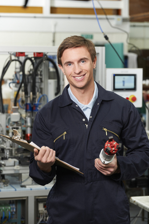 happy workers: Engineer Checking Component In Factory
