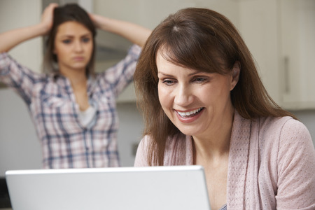 17 year old: Mother Using Laptop With Frustrated Daughter In Background
