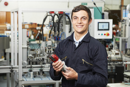 computerised: Apprentice Engineer Checking Component In Factory