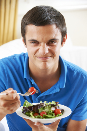 fussy: Teenage Boy Pulling Face Whilst Eating Healthy Salad