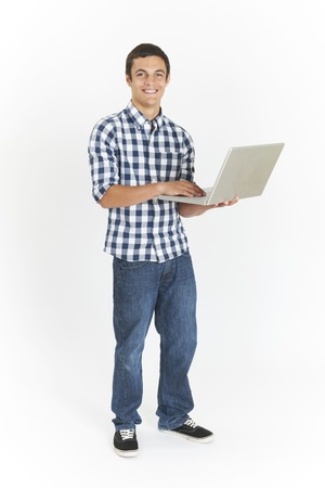 Full Length Cut Out Of Teenage Boy Using Laptop