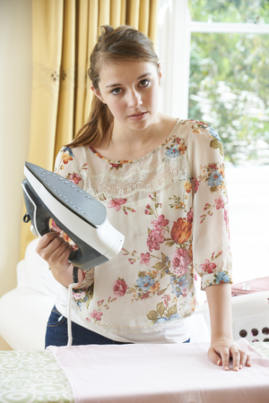 are fed: Fed Up Teenage Girl Ironing Clothes Stock Photo