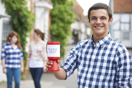 charity collection: Teenage Boy Collecting For Charity In Street