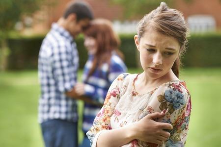 pareja de adolescentes: Solitaria Celoso Adolescente Con pareja romántica en el fondo