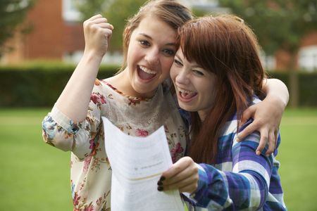 test result: Teenage Girls Celebrating Good Exam Result