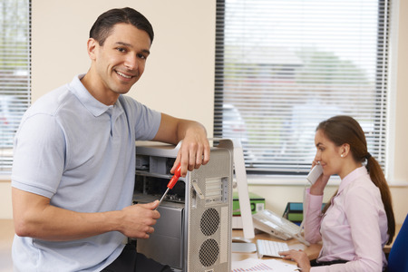 business support: Computer IT Support Worker Fixing Machine In Office Stock Photo