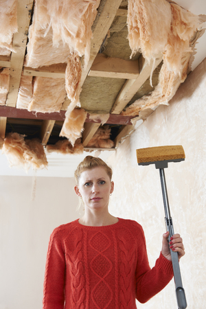 mid thirties: Woman Holding Mop Under Damaged Ceiling