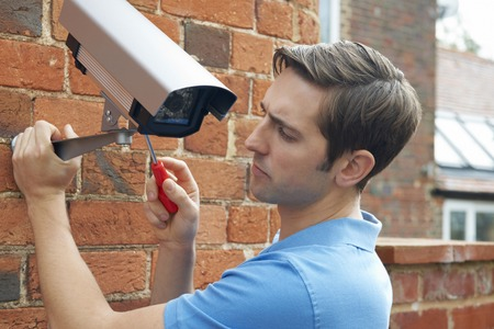 home security: Man Fitting Security Camera To House Wall