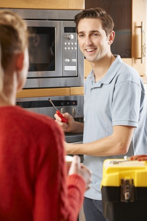 mid thirties: Engineer Giving Advice To Woman On Cooker Repair