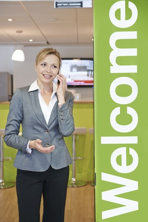 office entrance: Businesswoman On Mobile Phone By Office Entrance