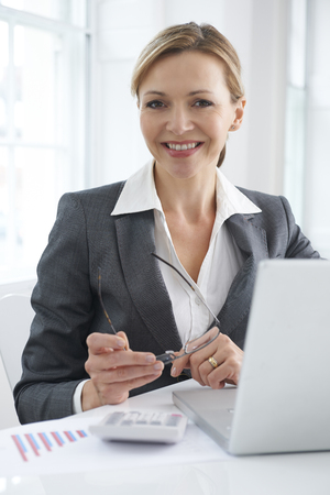 40s adult: Businesswoman Working On Laptop At Desk