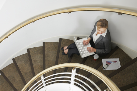 looking at computer: Businesswoman Sitting On Stairs Using Laptop