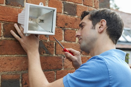 work from home: Man Fitting Security Light To Wall Of House Stock Photo