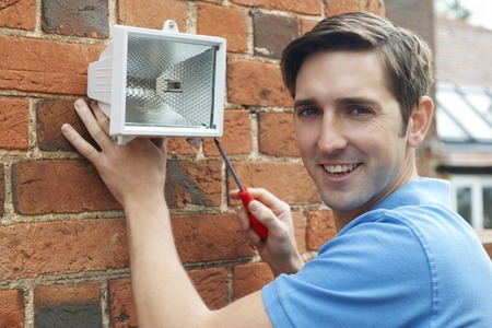 home security: Man Fitting Security Light To House Wall