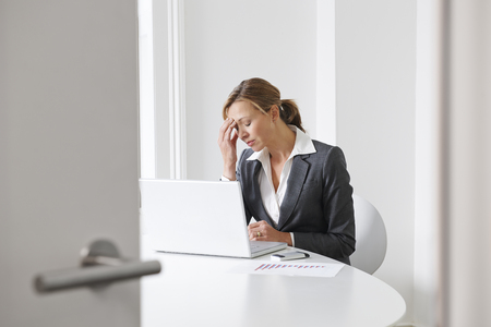 middle aged women: Stressed Businesswoman Working In Office Stock Photo