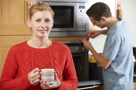 mid thirties: Woman Smiling As Cooker Is Repaired