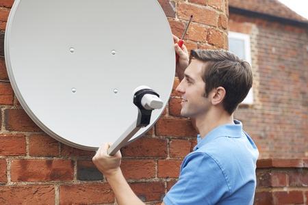 satellite tv: Man Fitting TV Satellite Dish To House Wall