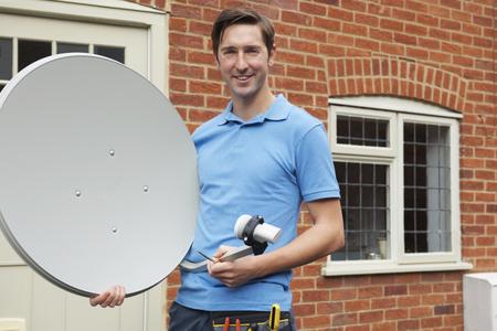 antena parabolica: Ingeniero Instalación de un plato de televisión por satélite Foto de archivo