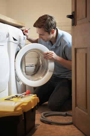 machine man: Engineer Mending Domestic Washing Machine Stock Photo