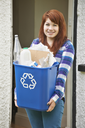 emptying: Teenage Girl Emptying Recycling At Home
