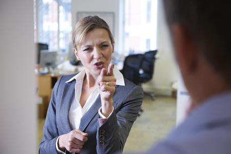 workplace harassment: Gritar agresiva Empresaria En colega masculino Foto de archivo