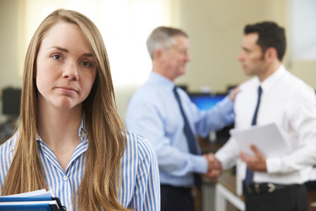 equal opportunity: Unhappy Businesswoman With Male Colleague Being Congratulated Stock Photo