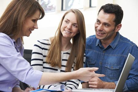 Couple Talking With Female Financial Advisor In Office Stock Photo